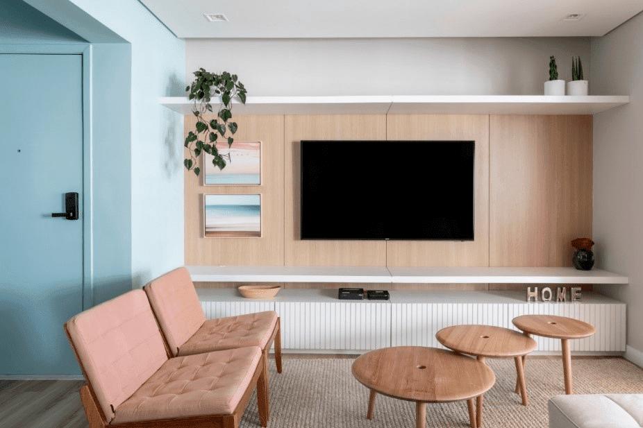 Azul clarinho é a cor dessa posta de entrada, em um apartamento com painel em madeira, tv na parede e um rack baixo branco