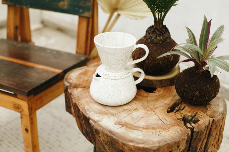 Mesinha em tronco de madeira, e em cima, duas Kokedamos, arranjos florais e um bule de café me cerâmica