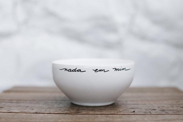 Bowl em porcelana branca escrito: nada em mim, em preto