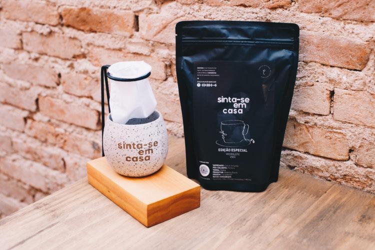 Mini coador de café e cima de uma caneca de cerâmica e um saco de pó de café, ambos com a frase: sinta-se me casa
