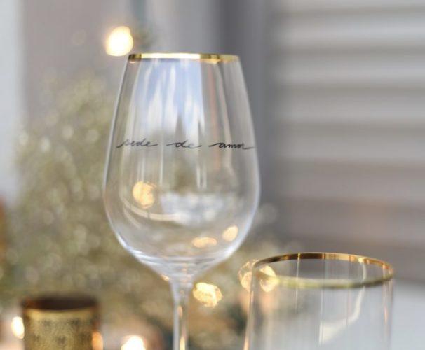Taça de vinho em cristal com a borda dourada e a frase: tenho fome de amor, escrito em preto