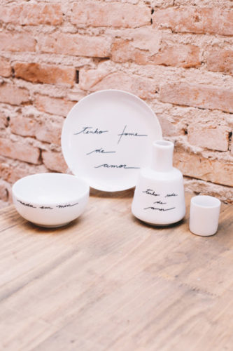 Prato, bowl e moringa em porcelana branca com a frase: tenho fome de amor, escrito em preto. AS peças estão encostadas em uma parede de tijolinho