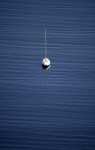 Exposição individual do fotógrafo Ari Kaye, foto do mar bem azul e no meio um veleiro branco