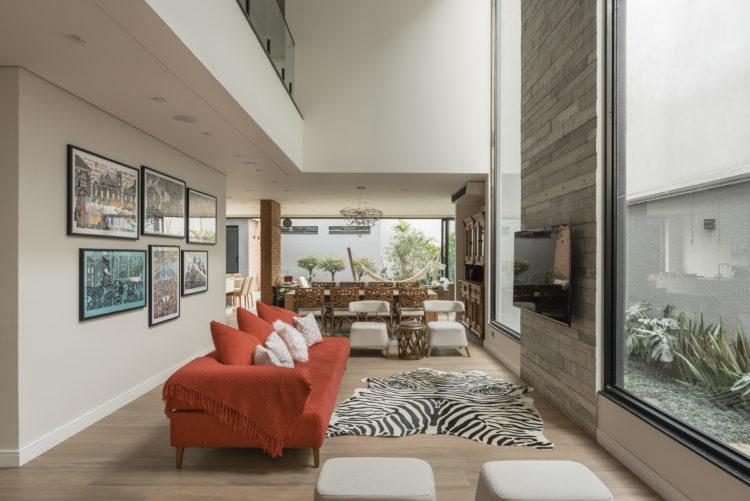 Decoração em diversos estilos nessa living com sofá vermelho, tapete de zebra e painel de porcelanato imitando madeira.