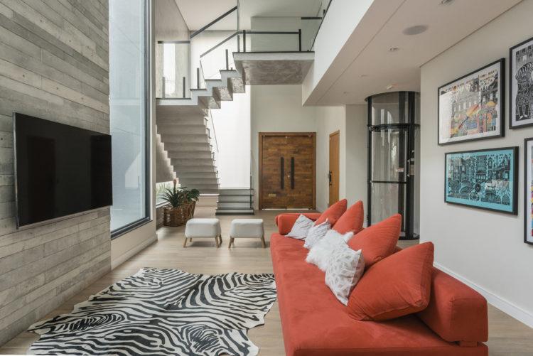 Decoração em diversos estilos nessa living com sofá vermelho, tapete de zebra e painel de porcelanato imitando madeira. Ao fundo escada em mármore, porta de entrada em madeira e ao lado elevador circular aparente.