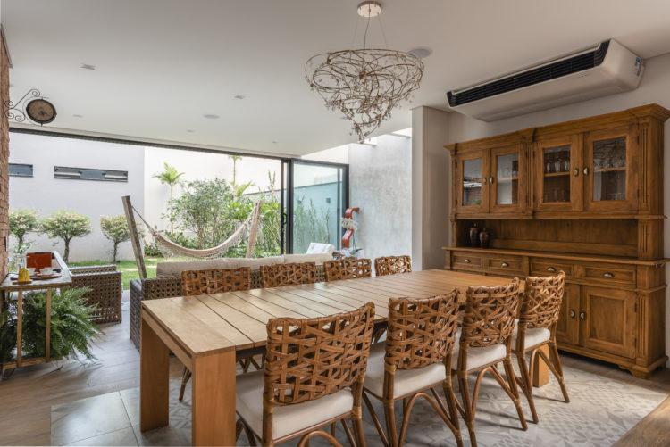Decoração em diversos estilos nessa sala de jantar. Mesa em madeira, cadeiras com trançados em vime e móvel rustico como aparador