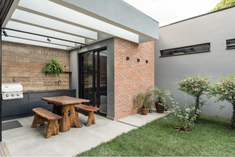 Área da churrasqueira aberta e integrada ao pequeno pátio com piso de grama. Bancada preta com parede de fundo no porcelanato imitando madeira,
