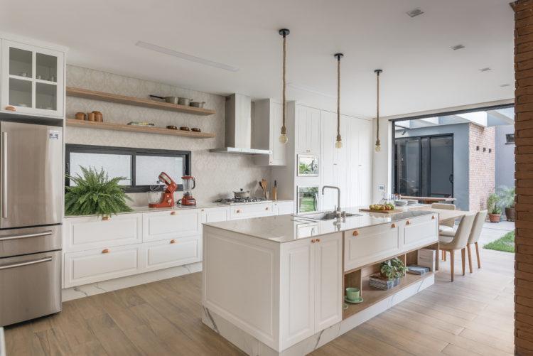 Cozinha com armários brancos no estilo provençal, ilha com cuba e mesa com cadeiras , totalmente integrada com a sala e aberta para o pequeno pátio.