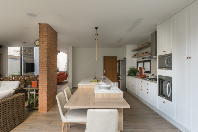 Cozinha totalmente integrada com a sala, armários brancos em estilo provençal, banca em ilha com cuba e mesa acoplada.