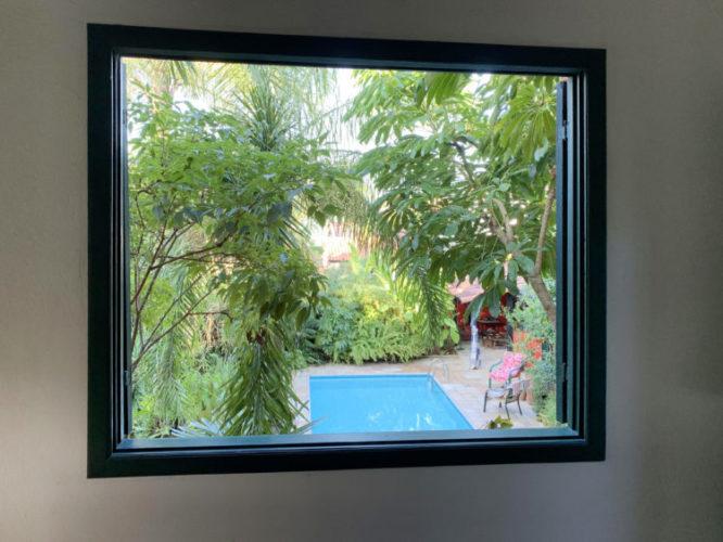 Foto de uma janela com vista exterior, para a piscina e o jardim , parecendo um quadro