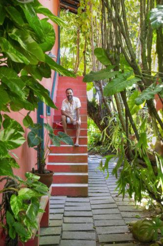 O arquiteto Francisco Palmeiro sentado na escada, da casa na região dos lagos. com jardim em torno