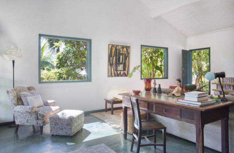 Sala de casa na região dos lagos, com paredes brancas, piso em cimento queimado, e janelas formatando o jardim lá fora.