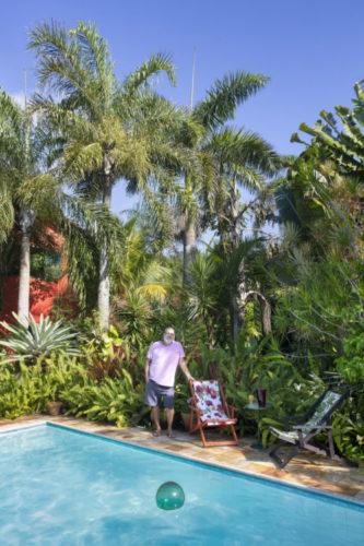 Foto do paisagista João Saldanha na beira da piscina na sua casa na região dos lagos, cercado por jardins exuberantes