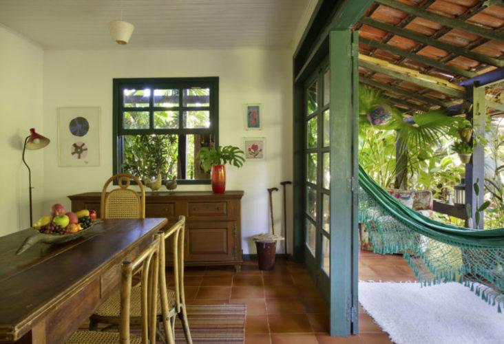 Sala de jantar em uma casa na região dos lagos, esquadrias verdes abertas para a varanda, teto de telhas e rede verde pendurada
