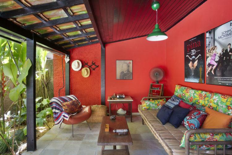 Varanda aberta , com as paredes pintadas na cor laranja, sofá com almofadas na estampa de chita, floral e colorida