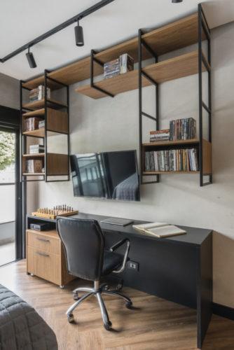 Bancada preta de home oficce, em cima estrutura de alumínio preto para prateleiras em madeira.