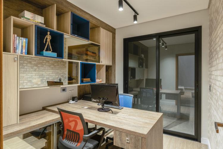 Escritorio com paredes revestidas em tijolinho, bancada em madeira apoiada de lado em prateleira compondo a estante com nichos em madeira e outros na cor azul.