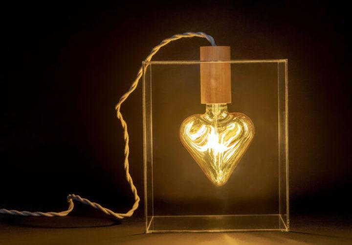 Lâmpada de filamento em formato de coração, bocal de madeira, dentro de uma caixa acrílica.