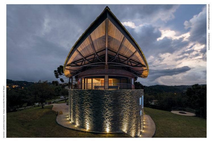Casa com arquitetura contemporânea, teto parecendo uma onda, com arvores araucárias em volta. Teto com uma ponta e iluminado, muro em pedra arredondado