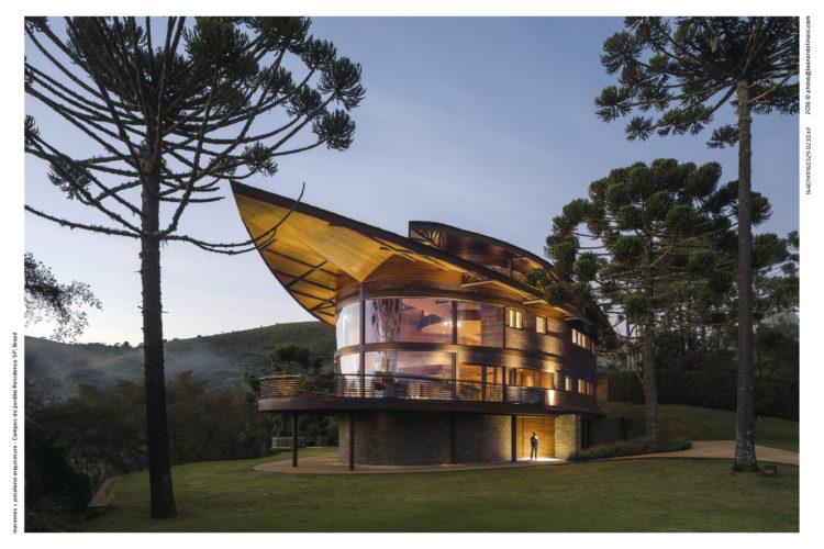 Casa com arquitetura contemporânea, teto parecendo uma onda, com arvores araucárias em volta. Teto com uma ponta e iluminado