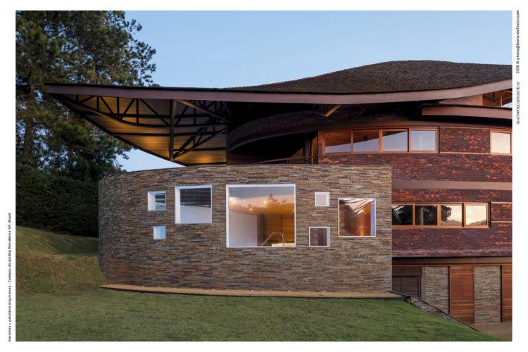 Fachada da casa, com arquitetura contemporânea, em pedra e com janelas quadradas. Telhado com uma onda na ponta