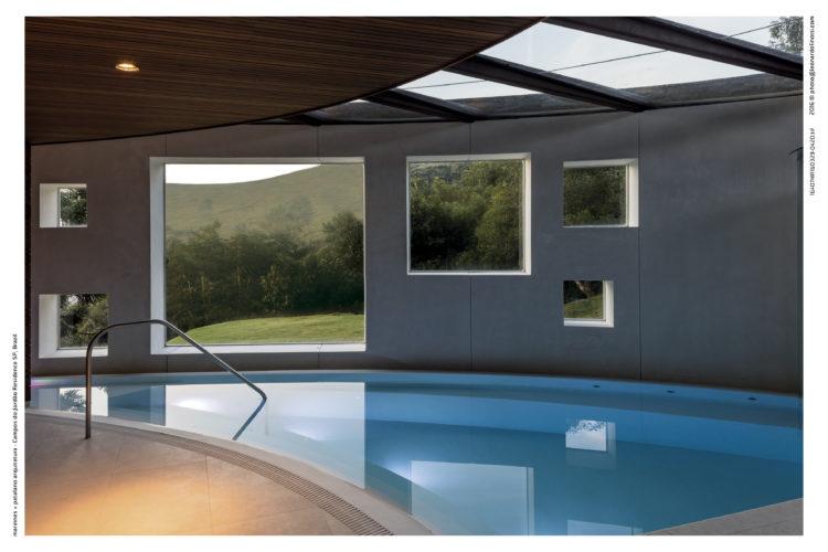 Casa com piscina interna e janelas quadradas para o exterior.