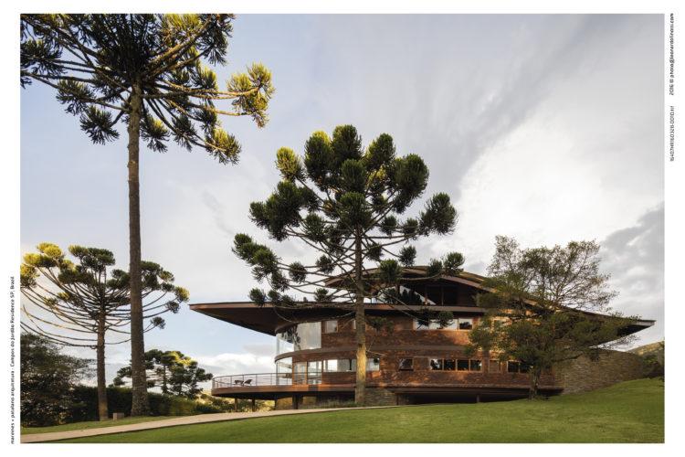 Casa com arquitetura contemporânea, teto parecendo uma onda, com arvores araucárias em volta