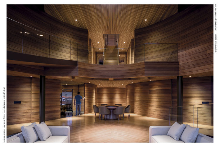 Interior de uma casa com arquitetura contemporânea. A casa tem quatro pavimentos e uma rampa no lugar de escadas, e paredes revestidas de ripas de peroba mica de tamanhos diferentes.