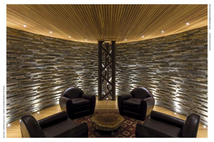 Interior de uma casa com arquitetura contemporânea. Espaço da Adega com paredes de pedra e teto com ripas de madeira.