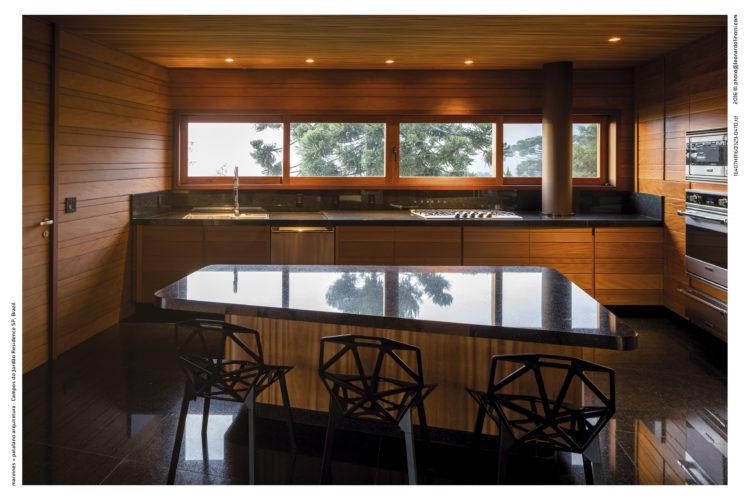 Cozinha toda revestida em madeira e uma bancada no meio , com tampo de granito preto.