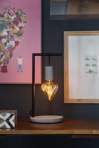 Base de concreto com um bocal do mesmo material e uma lâmpada de filamento em formato de coração