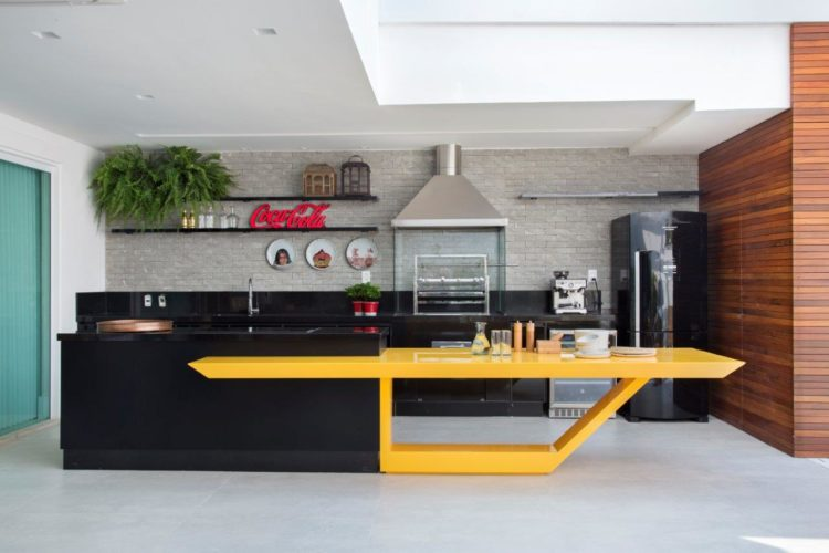 Área gourmet da cobertura, na frente bancada preta alta e ao lado, como se fosse continuação, ´so que mais baixa , um mesa na cor amarela. Ao fundo, bancada preta com cuba e churrasqueira e ao lado, geladeira preta.