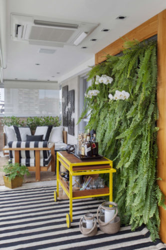 Varanda com parede viva de plantas, com samambaias, carrinho amarelo em frete, usado com bar, tapete listrado e ao fundo, sofá listrado