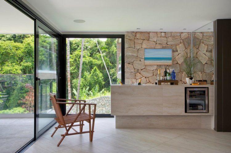 Espaço do bar na cobertura, ao fundo parede de pedra. Na frete bancada em mármore com geladeira de vinho embutida, janelões integram a natureza.