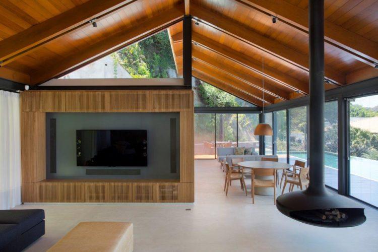 Casa na serra com projeto minimalista. Piso em concreto, uma lareira preta suspensa, teto em madeira.
