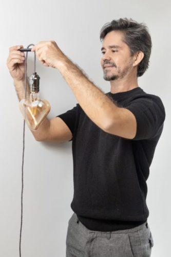 Arquiteto e designer Ric melo com a sua criação, lumiarias com lâmpadas de filamento em formato coração.