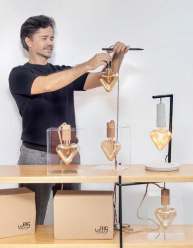 Ric Melo designer e arquiteto na foto segurando uma das suas luminárias