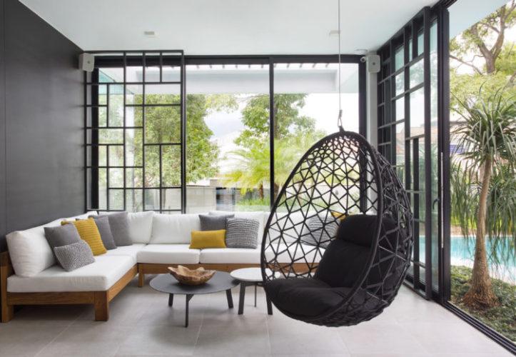Sala de estar, com vidros , integram a paisagem da piscina, Sofá em L branco e uma cadeira de balanço suspensa preta.