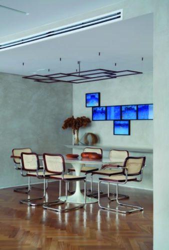 Sala de jantar com paredes na cor cinza, composição de quadros azuis em cima do aparador cinza, mesa oval Saarinen com tampo em mármore, cadeiras em palhinha.