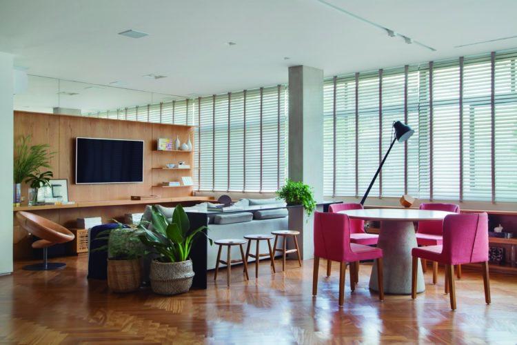 Ampla sala de estar, janelões com persianas na horizontal, parede revestida de madeira ao fundo, para abrigar a TV, no primeiro plano, mesa redonda com quatro cadeiras rosas.