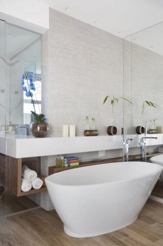 Banheira oval na cor branca no mio do banheiro, espelho na prede de fundo