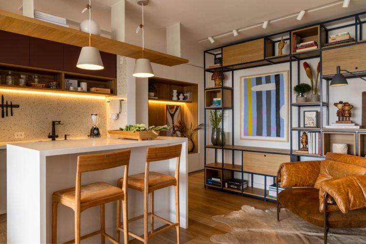 Varanda integrada no apartamento de 90m² na Zona Sul carioca. Cozinha também integrada, estante em ferro e poltrona em couro