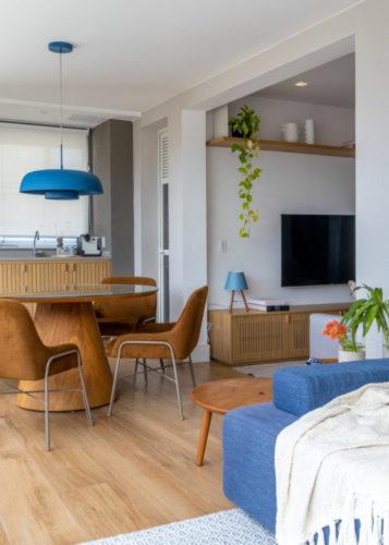 Varanda integrada no apartamento de 90m² na Zona Sul carioca. Sofá azul, mesa redonda com cadeiras em couro