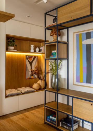 Parede de armários e no meio, nicho em madeira com futons , criando assentos.