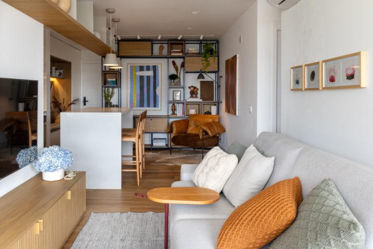 Sala comprida e estreita com sofá claro e em frente tv na parede e rack baixo em madeira. Ao fundo, estante em ferro e cozinha integrada a sala com balcão alto.