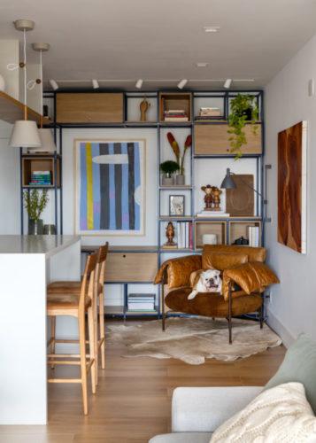 Sala com estante em ferro ao fundo, e na frente uma poltrona em couro com cachorro em cima