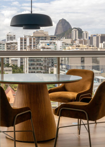 Varanda integrada no apartamento de 90m² na Zona Sul carioca, com vista para o pão de açúcar ao fundo. Mesa redonda com pé central, cadeiras em couro marrom e pendente na cor azul no centro