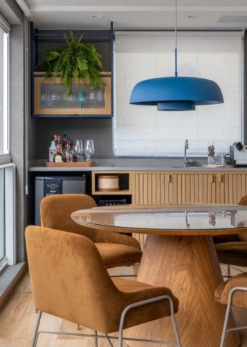 Varanda integrada no apartamento de 90m² na Zona Sul carioca Mesa de jantar redonda, ao fundo bancada com cuba e mini geladeira