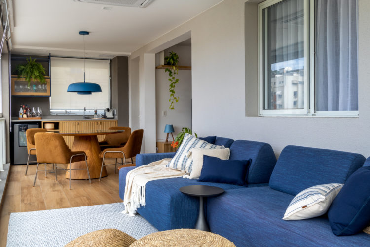 Varanda integrada no apartamento de 90m² na Zona Sul carioca. Sofá azul, ao fundo mesa de jantar redonda com cadeiras em couro, bancada com cuba e mini geladeira