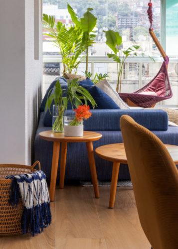 Na varanda, sofá azul, ao fundo cadeira de balanço pendente